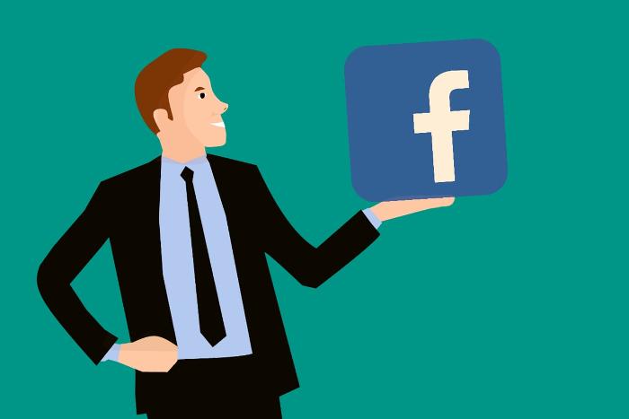 Mann hält Facebook-Symbol in der Hand
